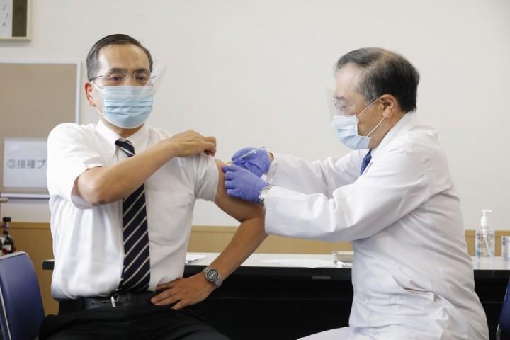 Leyenda: Kazuhiro Araki (izq.), Director del Centro Médico de Tokio, es vacunado por un colega en su propio hospital ubicado en el distrito de Meguro, convirtiéndose en la primera persona en ser vacunada en Japón. (Foto: Kyodo News)